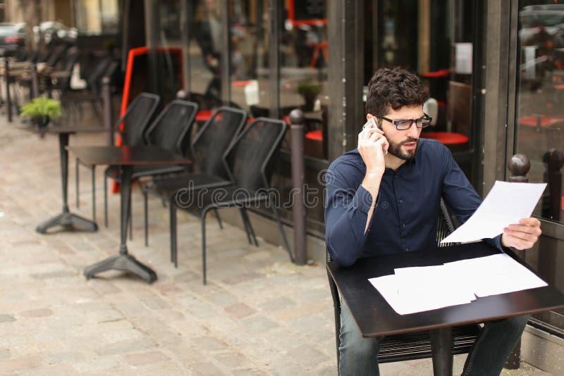 Geschäftsmann, der durch Smartphone argumentiert und Papiere am Cafévorsprung liest stockfotos