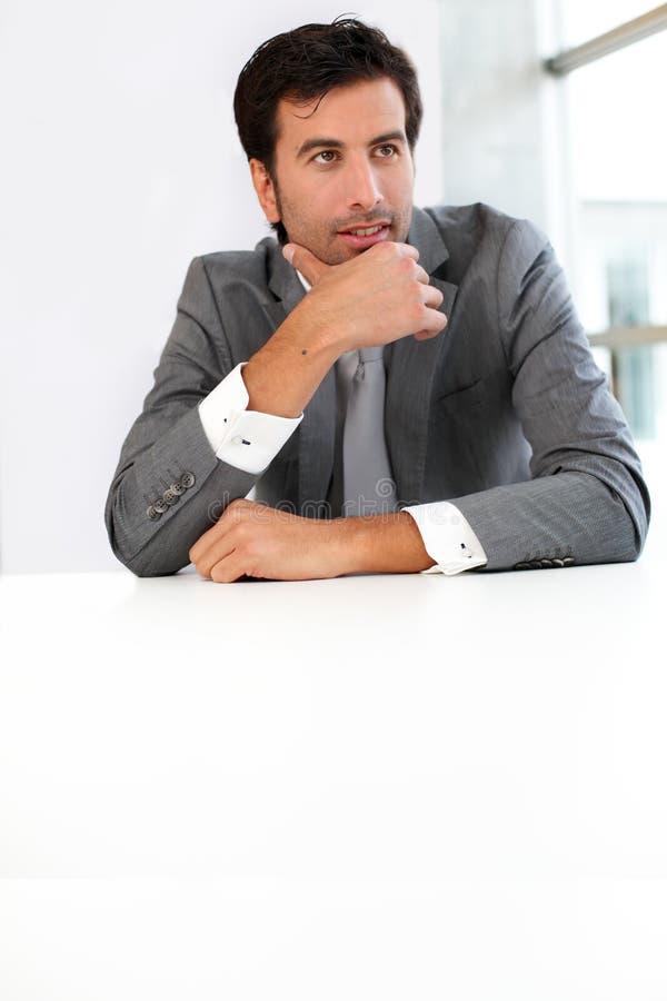 Geschäftsmann, der durch thee Schreibtisch sitzt lizenzfreie stockfotografie