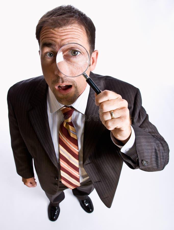 Geschäftsmann, der durch Vergrößerungsglas schaut lizenzfreies stockbild