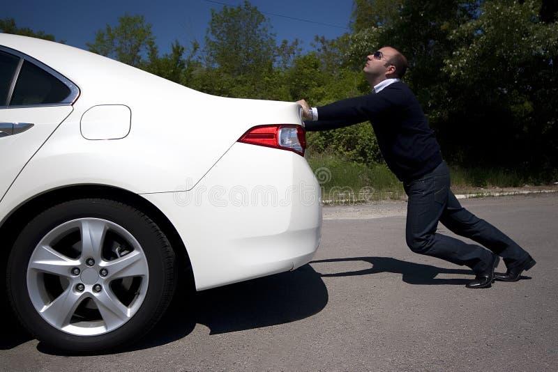 Geschäftsmann, der ein Auto drückt stockfotografie