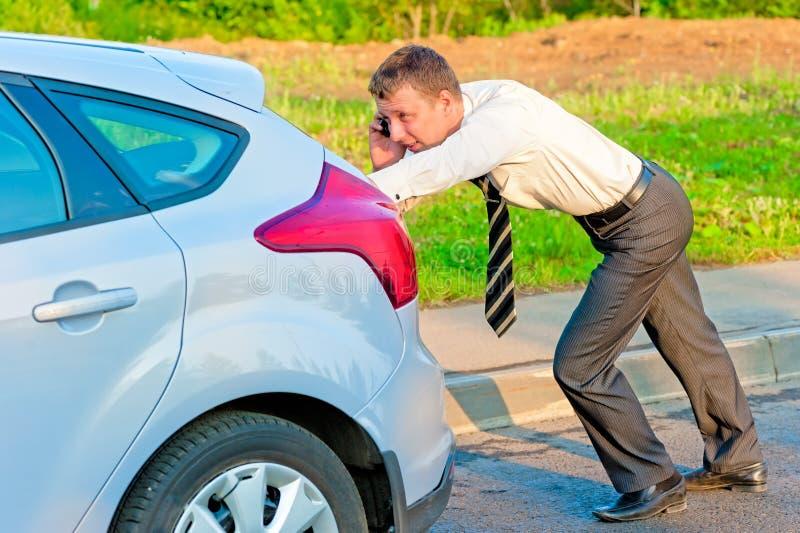 Geschäftsmann, der ein Auto drückt und am Telefon spricht stockfoto