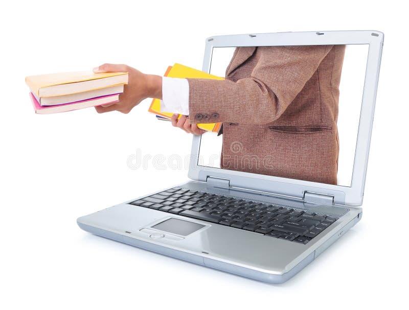 Geschäftsmann, der ein Buch und aus dem Laptop heraus trägt lizenzfreies stockbild