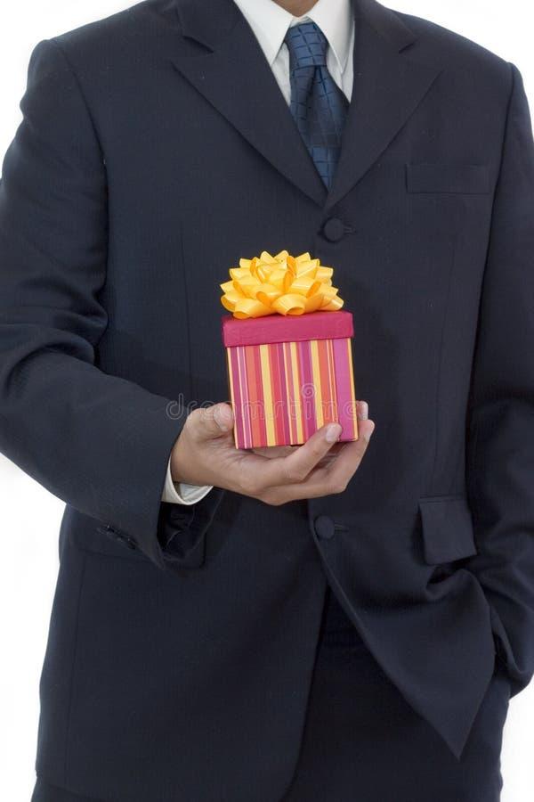 Geschäftsmann, der ein Geschenk anhält stockfotos