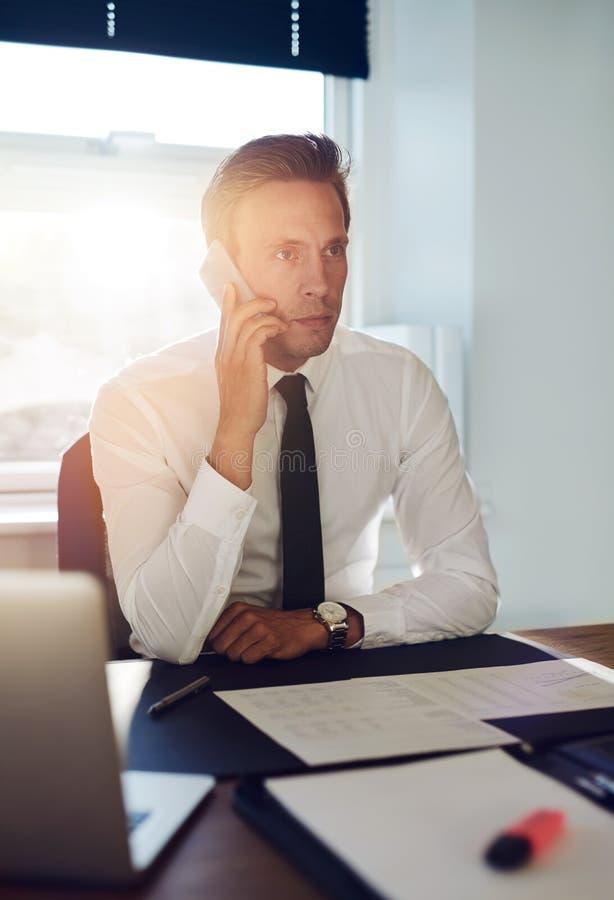Geschäftsmann, der ein Gespräch am Telefon hat stockbild
