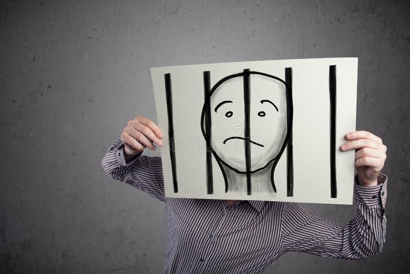 Geschäftsmann, der an ein Papier mit einem Gefangenen hinter den Stangen I hält stockfoto