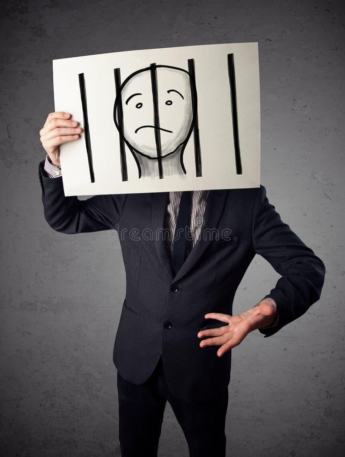 Geschäftsmann, der an ein Papier mit einem Gefangenen hinter den Stangen I hält lizenzfreie stockbilder