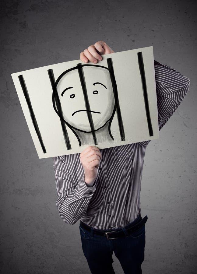 Geschäftsmann, der an ein Papier mit einem Gefangenen hinter den Stangen I hält lizenzfreie stockfotos