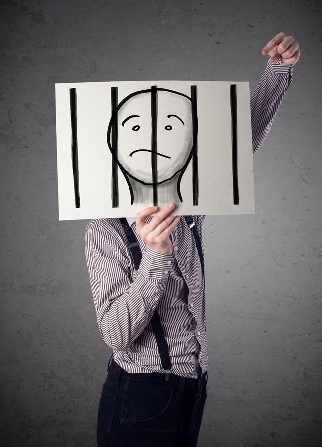 Geschäftsmann, der an ein Papier mit einem Gefangenen hinter den Stangen I hält stockfotografie