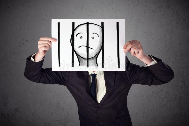 Geschäftsmann, der an ein Papier mit einem Gefangenen hinter den Stangen I hält stockbilder