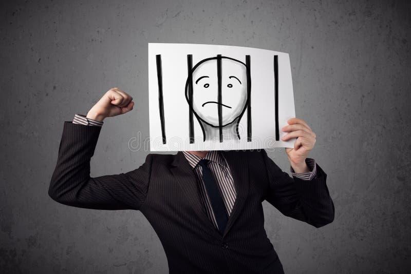 Geschäftsmann, der an ein Papier mit einem Gefangenen hinter den Stangen I hält stockbild