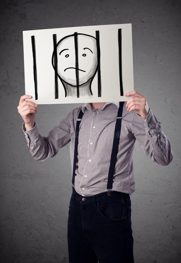 Geschäftsmann, der an ein Papier mit einem Gefangenen hinter den Stangen I hält lizenzfreie stockfotografie