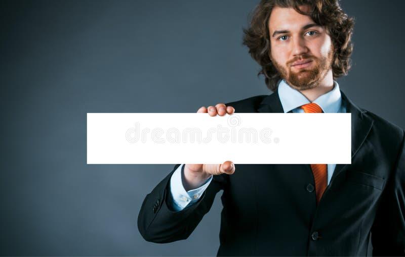 Geschäftsmann, der ein rechteckiges leeres Zeichen hält stockfoto