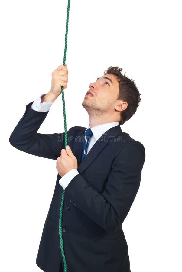 Geschäftsmann, der ein Seil steigt stockbild