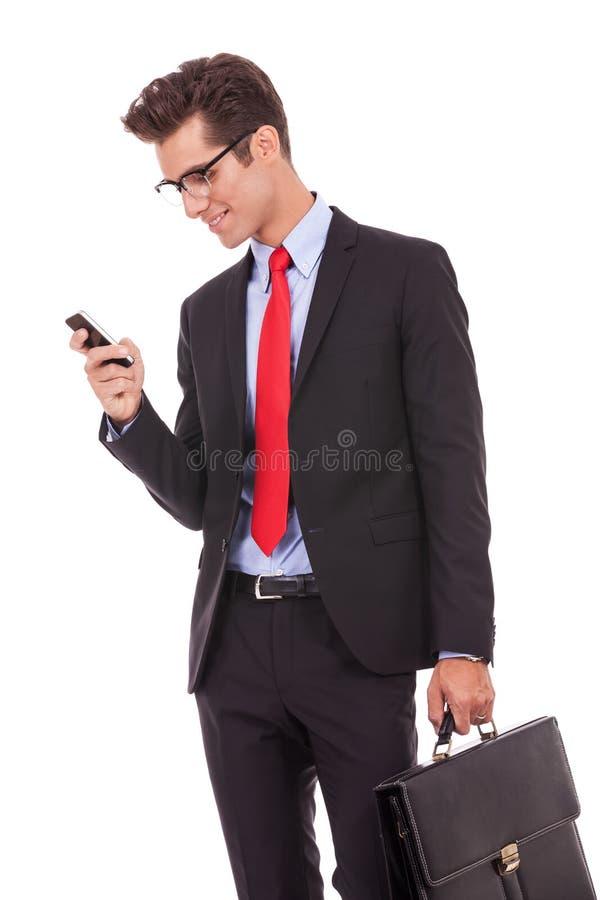 Geschäftsmann, der ein SMS auf smartphone liest stockbild