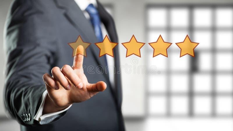 Geschäftsmann, der eine Bewertung mit fünf Sternen gibt stockfotografie
