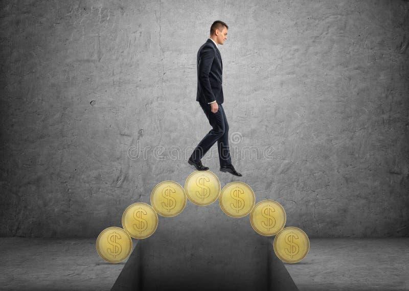 Geschäftsmann, der eine Brücke hergestellt von den goldenen Münzen kreuzt stockfotografie