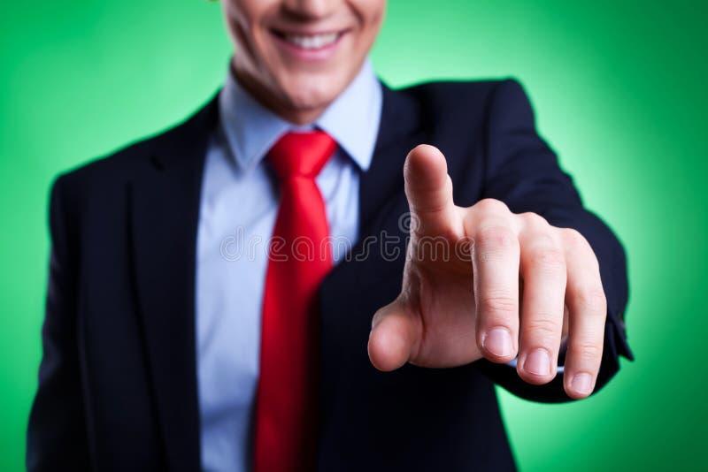 Geschäftsmann, der eine eingebildete Taste bedrängt stockbild