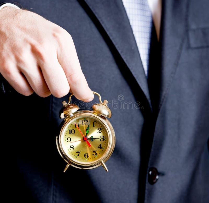 Geschäftsmann, der eine goldene Borduhr anhält stockbild