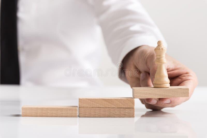 Geschäftsmann, der eine Königinschachfigur auf einem Block hält stockfotografie
