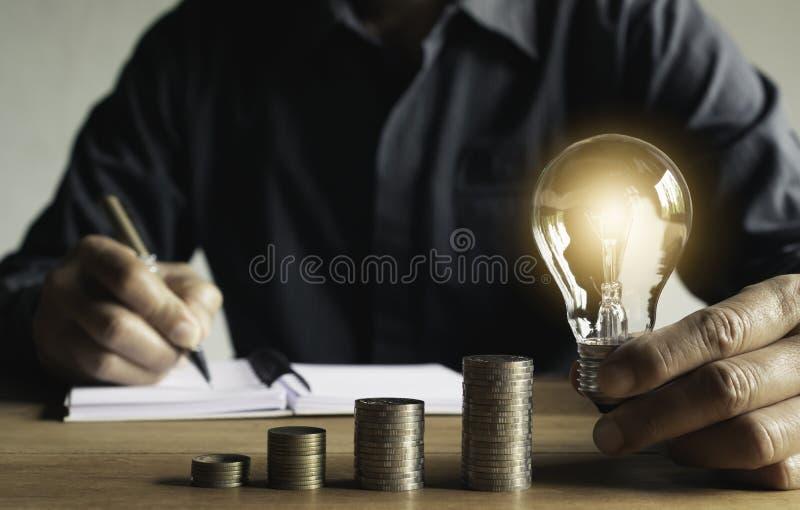 Geschäftsmann, der eine Münze auf Münzenstapel-Sparkasse und sein Geld alles erklären in Finanzbilanzauffassung einsetzt stockbilder
