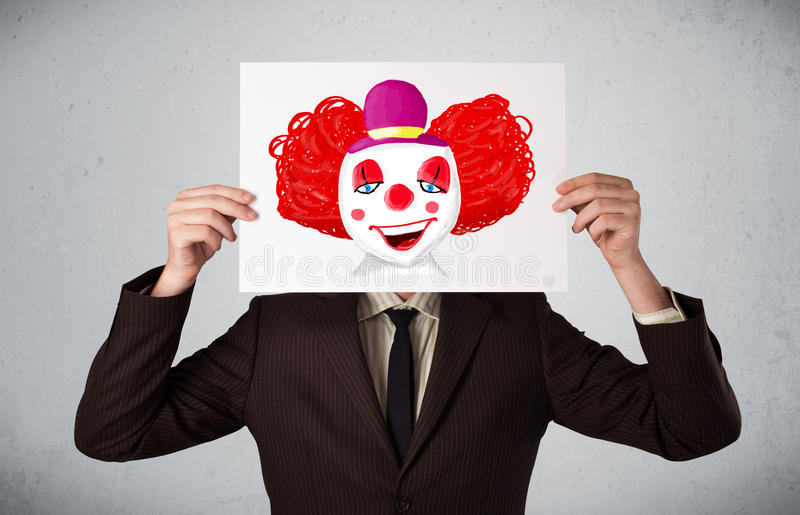 Geschäftsmann, der eine Pappe mit einem Clown auf ihr vor h hält stockfoto