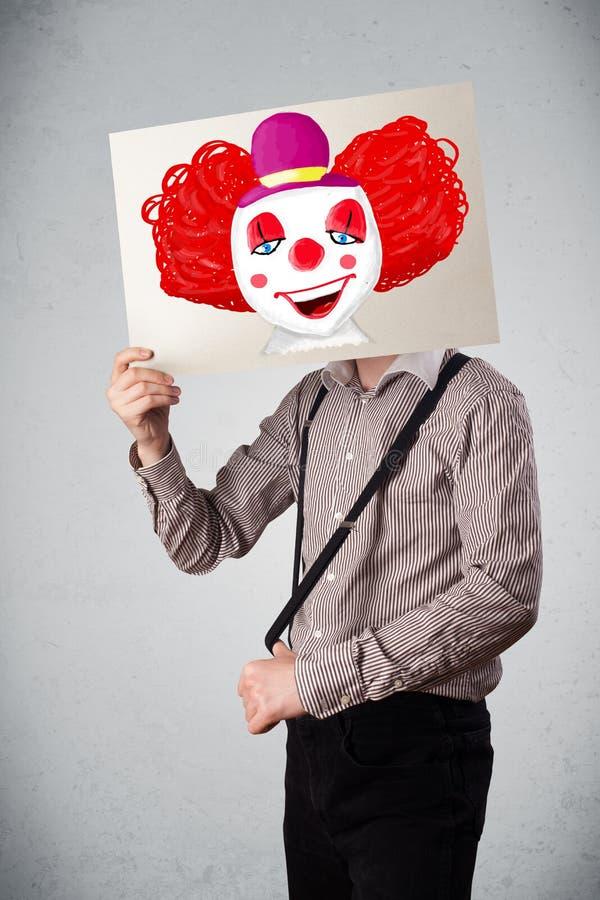 Geschäftsmann, der eine Pappe mit einem Clown auf ihr vor h hält lizenzfreie stockfotos