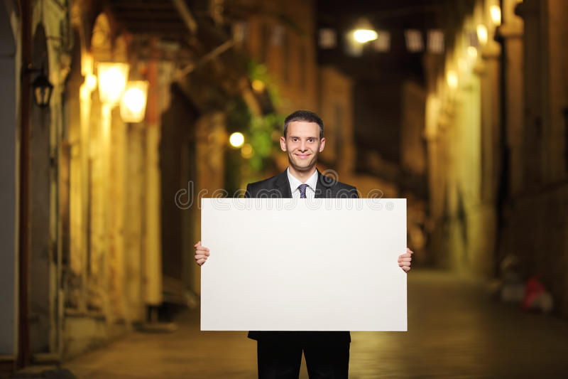 Geschäftsmann, der eine Platte in einer Stadtstraße hält lizenzfreie stockfotos