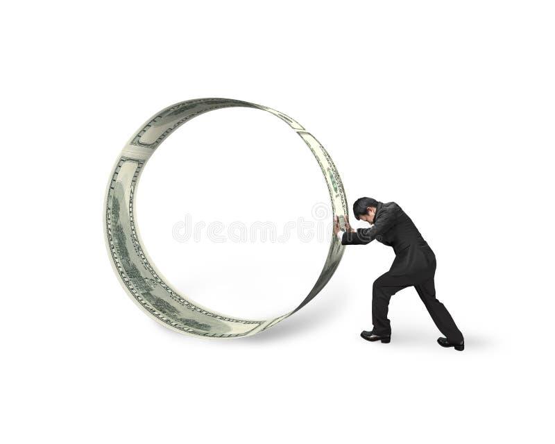 Geschäftsmann, der eine Rolle von Dollarscheinen drückt lizenzfreie stockbilder