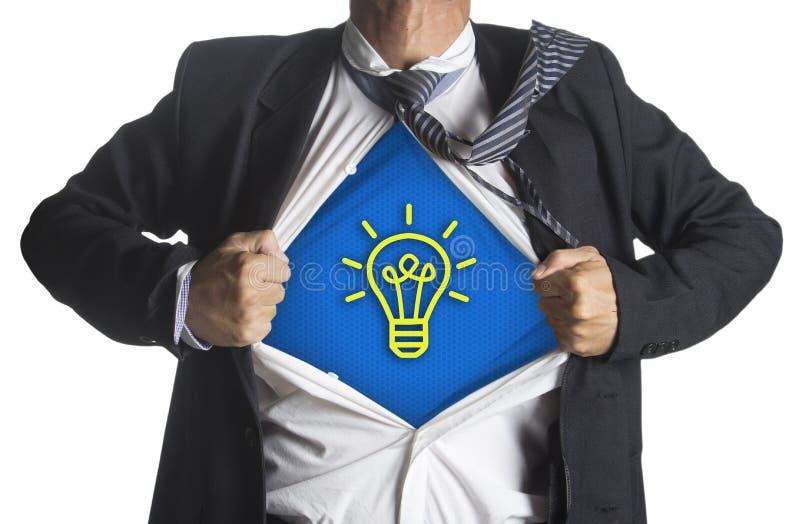 Geschäftsmann, der eine Superheldklage unter Glühlampe der Idee zeigt lizenzfreies stockfoto