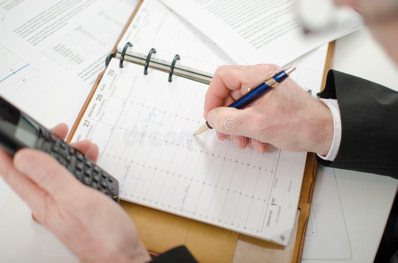 Geschäftsmann, der eine Verabredung in seinem Tagebuch nimmt stockbild