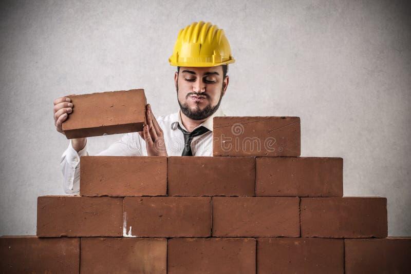 Geschäftsmann, der eine Wand errichtet lizenzfreies stockbild