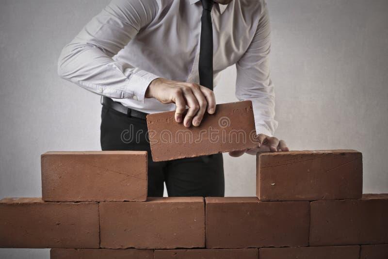 Geschäftsmann, der eine Wand errichtet lizenzfreie stockbilder