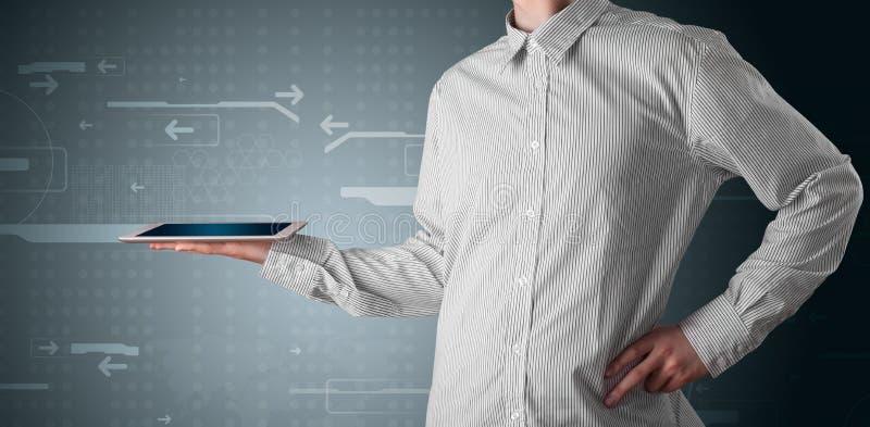 Geschäftsmann, der eine weiße moderne Tablette mit undeutlichen apps anhält stockbild