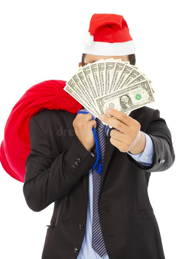 Geschäftsmann, der eine Weihnachtsgeschenktasche und -geld hält lizenzfreie stockfotografie