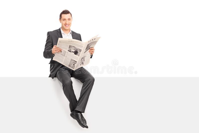Geschäftsmann, der eine Zeitung gesetzt auf einer Platte hält stockbild
