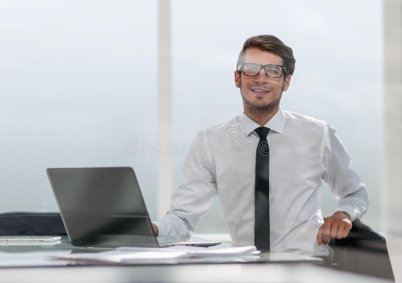 Geschäftsmann, der in einem geräumigen Büro sitzt lizenzfreie stockfotografie
