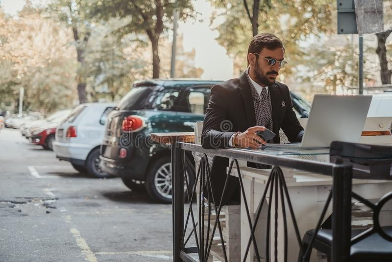 Geschäftsmann, der an einem Laptop arbeitet und Handy hält stockfotos