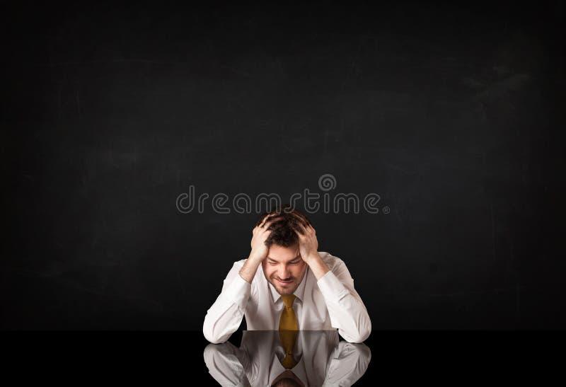Geschäftsmann, der an einem Schreibtisch sitzt stockbild