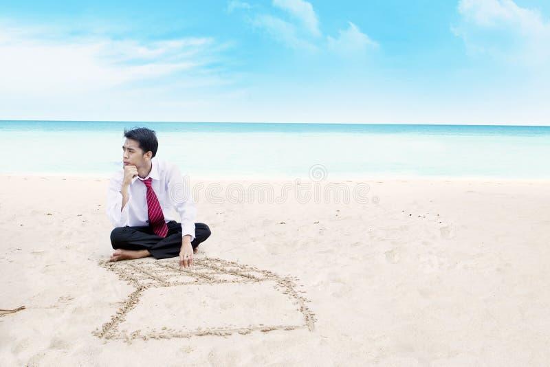 Geschäftsmann, der an einem Strand denkt lizenzfreie stockfotografie