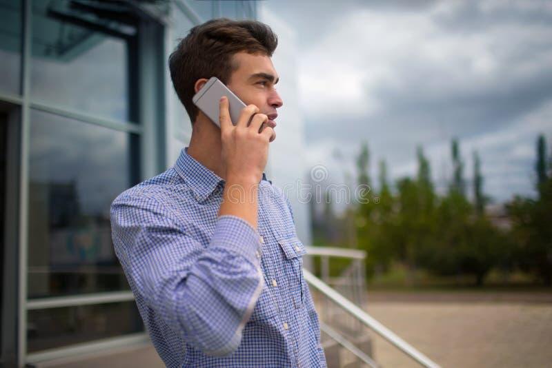 Geschäftsmann, der an einem Telefon spricht Hübscher Kerl, der ein Telefon auf einem unscharfen Hintergrund nennt Gesprächskonzep lizenzfreie stockfotos