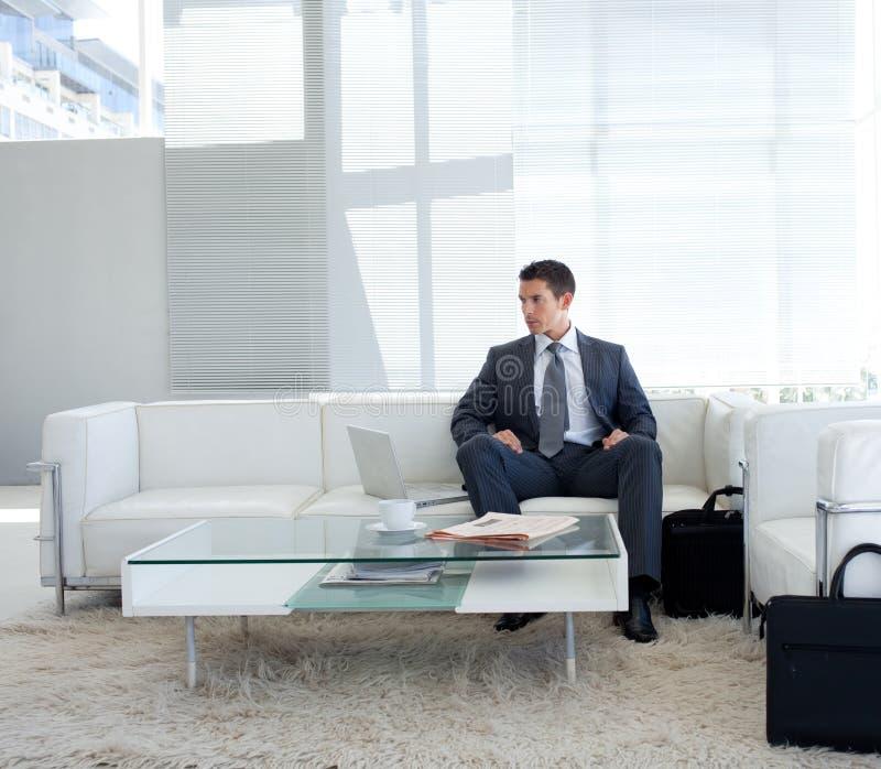 Geschäftsmann, der in einem Warteraum sitzt lizenzfreie stockbilder