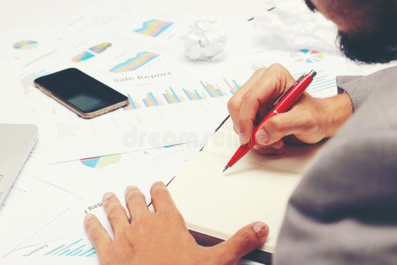 Geschäftsmann, der einen Geschäftsbericht auf leeres Notizbuch mit rotem Stift auf Schreibtischbüro schreibt Geschäftskonzept: lizenzfreies stockfoto