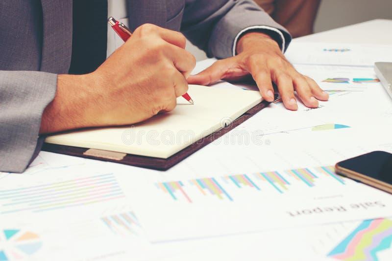 Geschäftsmann, der einen Geschäftsbericht auf leeres Notizbuch mit rotem Stift auf Schreibtischbüro schreibt Geschäftskonzept: stockbild