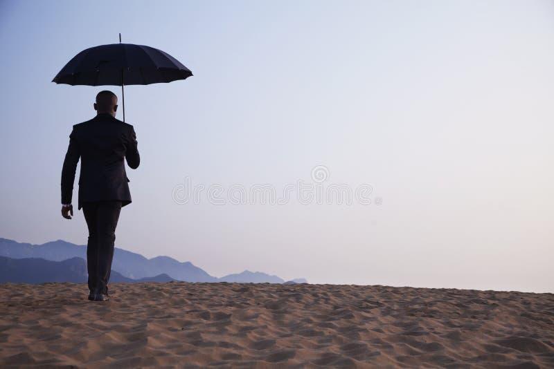 Geschäftsmann, der einen Regenschirm hält und weg mitten in der Wüste geht lizenzfreies stockbild