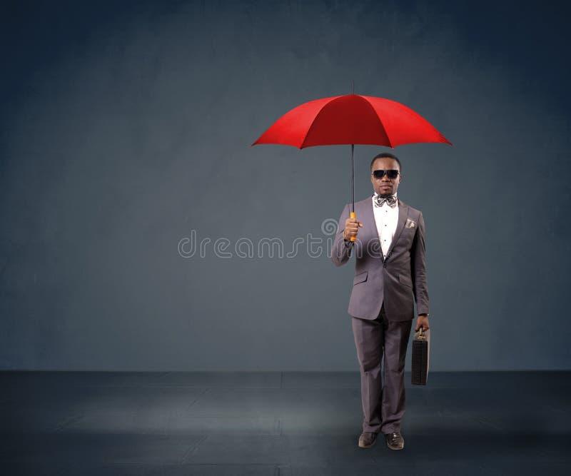 Geschäftsmann, der einen roten Regenschirm hält stockfotografie