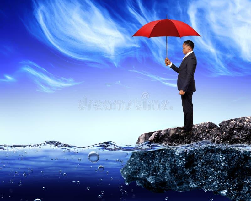 Geschäftsmann, der einen roten Regenschirm hält stockfotos
