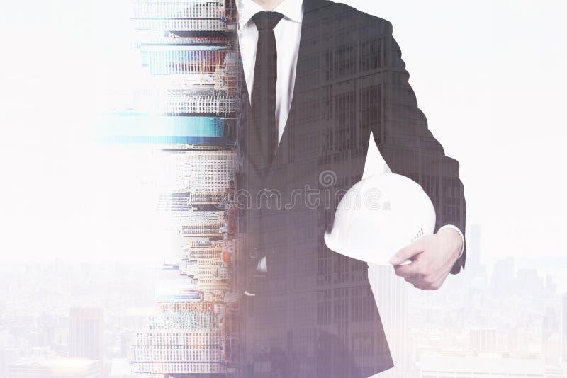 Geschäftsmann, der einen Schutzhelm hält lizenzfreies stockfoto