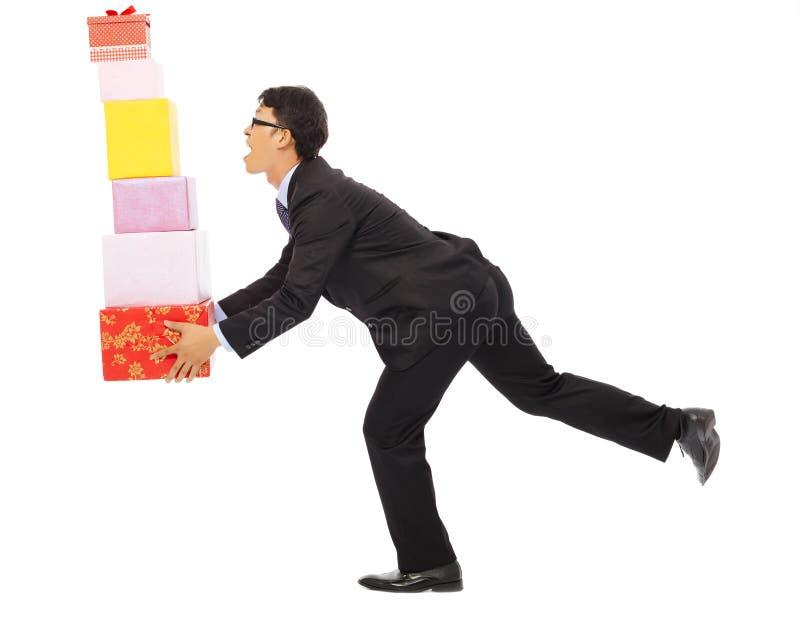 Geschäftsmann, der einige Geschenkboxen hält Lokalisiert auf Weiß stockfoto