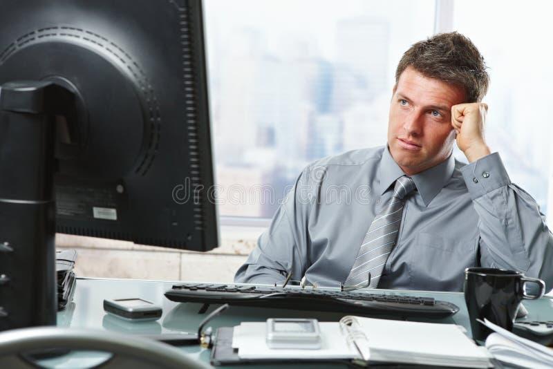 Geschäftsmann, der Entscheidung im Büro trifft stockfotografie