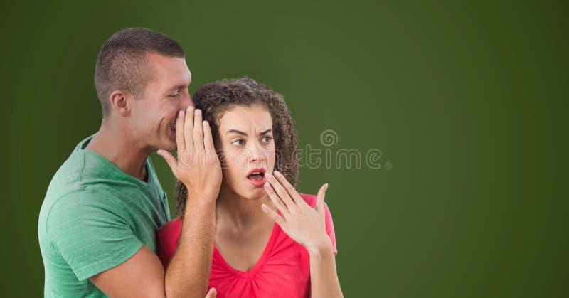Geschäftsmann, der in entsetztem Kollege ` s Ohr gegen grünen Hintergrund flüstert stockfotografie